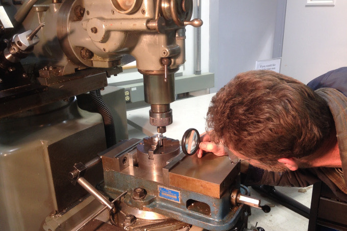 a machinist uses a handheld magnifying glass to inspect an end mill